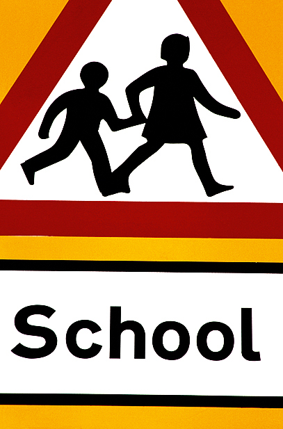 A road sign in front of school
