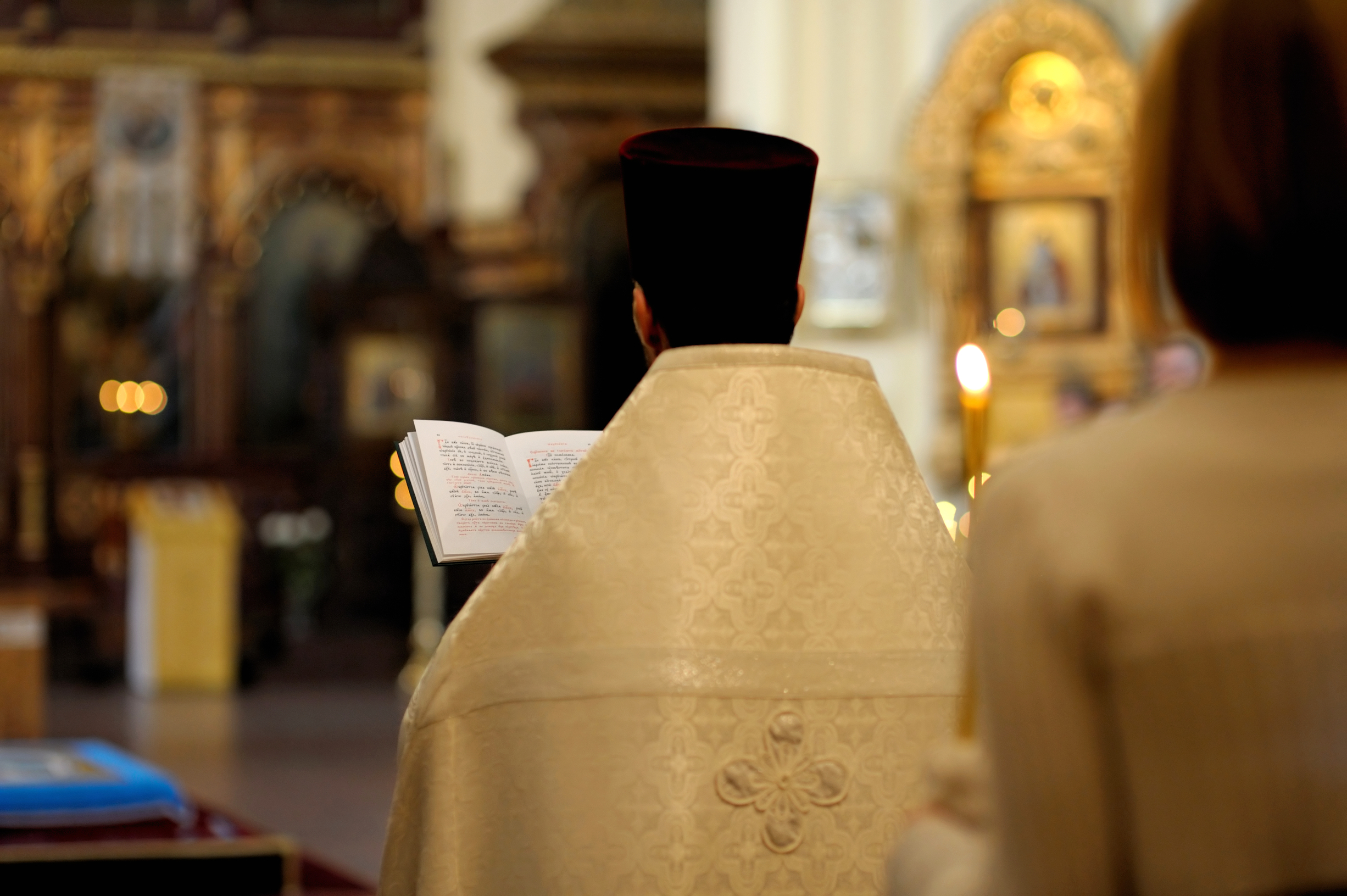 Orthodox priest reading Holy Book during wedding ceremony in a church