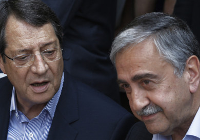 Cyprus President Nicos Anastasiades, left, and Turkish Cypriot leader Mustafa Akinci, speak as they sit at a coffee shop at the Turkish Cypriot breakaway northern part of the Cypriot divided capital Nicosia on Saturday, May 23, 2015. Cyprus' rival Greek and Turkish Cypriot leaders took a stroll together on both sides of the divided capital's medieval center to raise the feel-good factor as talks aimed at reunifying the ethnically split island kick into gear. It's the first time that the leaders have done so together since the east Mediterranean island was split in 1974 when Turkey invaded after coup by supporters of union with Greece. (AP Photo/Petros Karadjias)
