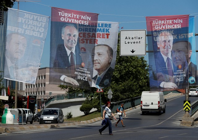 People walk under elelction posters for Turkey's President Tayyip Erdogan and Muharrem Ince, Presidential candidate of Turkey's main opposition Republican People's Party (CHP)  in Istanbul, Turkey June 13, 2018. REUTERS/Osman Orsal