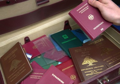 epa04206577 A police officer holds a passport from a suitcase found during a raid in Berlin-Neukoelln, Germany, 15 May 2014. An Islamic funeral home in the Berlin district of Neukoelln is said to have sold passports of dead to traffickers. In the large-scale raid police searched 26 properties in Berlin.  EPA/PAUL ZINKEN